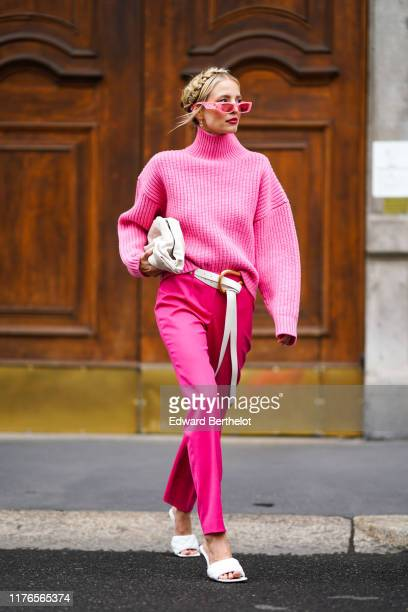 Leonie Hanne wears pink sunglasses, a pink wool turtleneck pullover, a white bag, a white belt, pink pants, white sandals, outside the Boss show...
