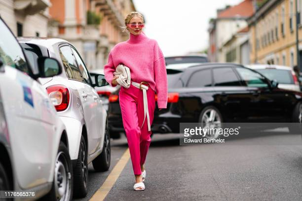 Leonie Hanne wears pink sunglasses a pink wool turtleneck pullover a white bag a white belt pink pants white sandals outside the Boss show during...