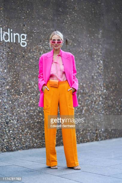 Leonie Hanne wears pink sunglasses earrings a pink blazer jacket a pink shirt orange flare pants an orange Jacquemus belt bag during London Fashion...