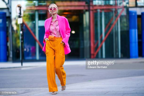 Leonie Hanne wears pink sunglasses, earrings, a pink blazer jacket, a pink shirt, orange flare pants, an orange Jacquemus belt bag, during London...