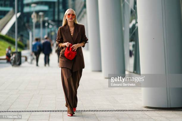 Leonie Hanne wears red transparent sunglasses, a brown oversized blazer jacket, a red bag, flared pants, red shoes, a necklace, outside the Alberta...