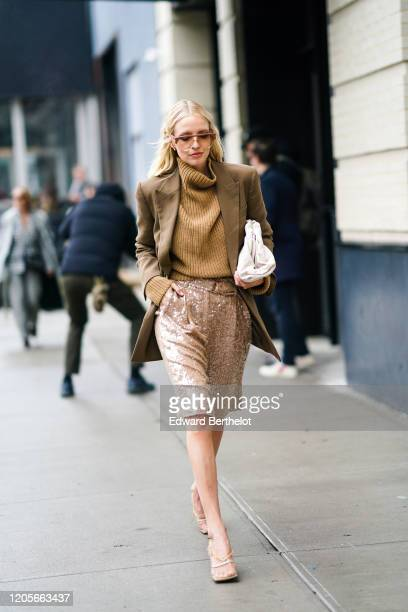 Leonie Hanne wears sunglasses, a brown oversized blazer jacket, a brown wool pullover, a glittering shiny skirt, sandals, a white puff bag, during...