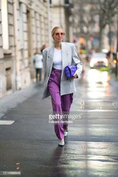 Leonie Hanne wears sunglasses, a gray oversized blazer jacket, a white top, purple flowing suit pants, shoes, a purple quilted Bottega Veneta bag,...