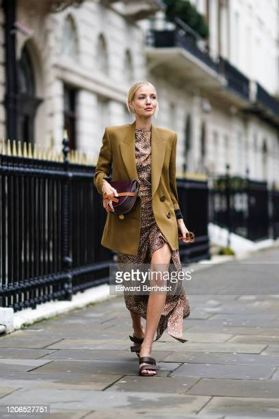 Leonie Hanne wears sunglasses a green khaki oversized blazer jacket a Loewe bag a brown flowing dress with printed polka dots sandals during London...
