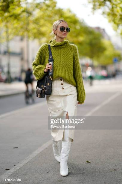 Leonie Hanne wears sunglasses, a green wool turtleneck knitted pullover, a Givenchy bag, white side slit skirt, white boots, outside Beautiful...