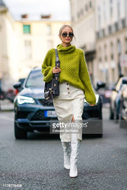Leonie Hanne wears sunglasses a green wool turtleneck knitted pullover a Givenchy bag white side slit skirt white high boots outside Beautiful People...