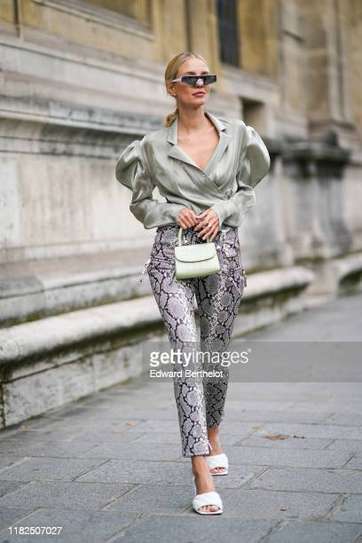 Leonie Hanne wears sunglasses, a lustrous light green wrap shirt with puff long sleeves and a plunging neckline, a light green handbag, grey python...
