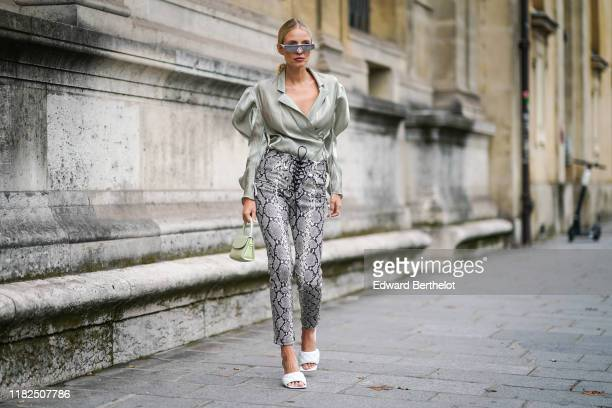 Leonie Hanne wears sunglasses a lustrous light green wrap shirt with puff long sleeves and a plunging neckline a light green handbag grey python...