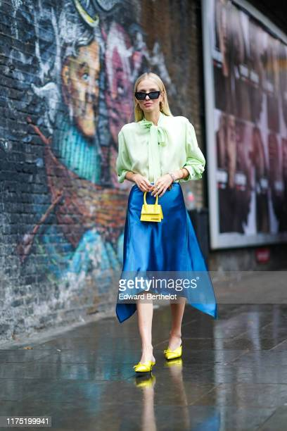 Leonie Hanne wears sunglasses, a neon green lustrous shirt, a yellow Jacquemus mini bag, a blue lustrous shiny skirt, yellow shoes, jewellery, during...