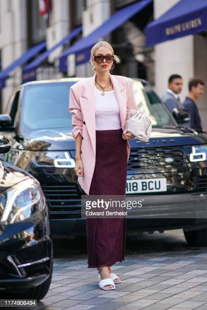 Leonie Hanne wears sunglasses, a pink oversized blazer jacket, a necklace, a white top, a purple wool skirt, white sandals, a bag, during London...