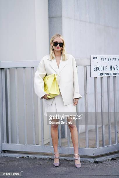 Leonie Hanne wears sunglasses an oversized white blazer jacket a yellow bag a white skirt bejeweled shoes outside BOSS during Milan Fashion Week...