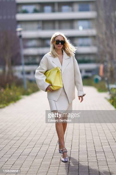 Leonie Hanne wears sunglasses, an oversized white blazer jacket, a yellow bag, a white skirt, bejeweled shoes, outside BOSS, during Milan Fashion...