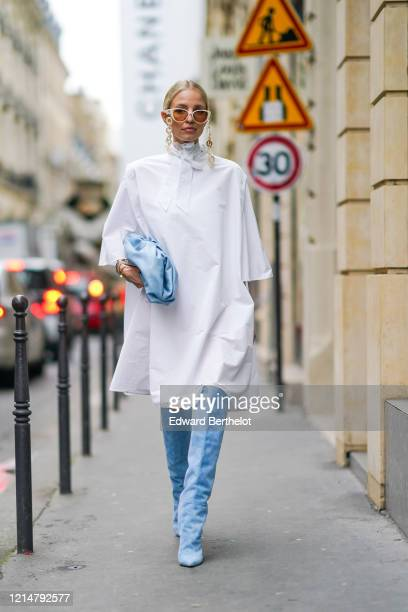 Leonie Hanne wears white sunglasses with chains, a white long dress, a pale blue puff Bottega Veneta bag, blue suede thigh high pointy boots, outside...