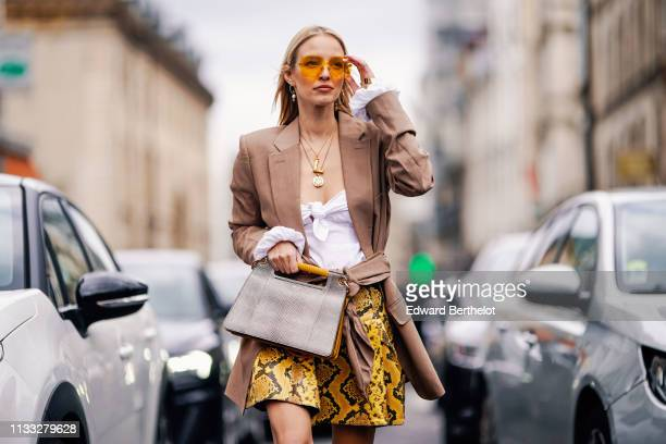 Leonie Hanne wears yellow sunglasses, a blazer jacket, a golden necklace, a white top, a yellow pvc snake print skirt, a gray bag, black boots,...