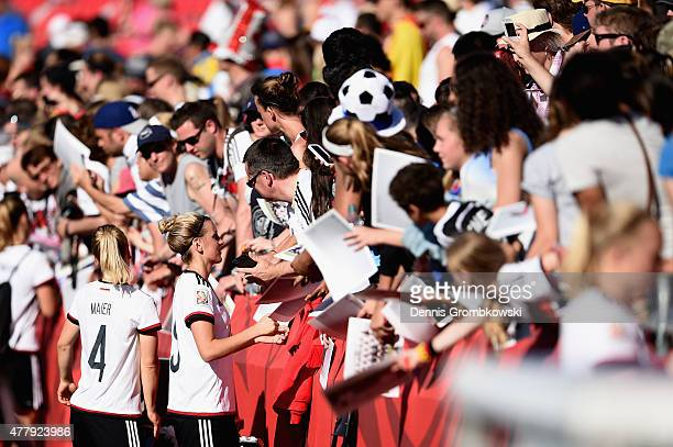 Leonie Maier and Jennifer Cramer of Germany sign autographs after the FIFA Women's World Cup Canada 2015 Round of 16 match between Germany and Sweden...