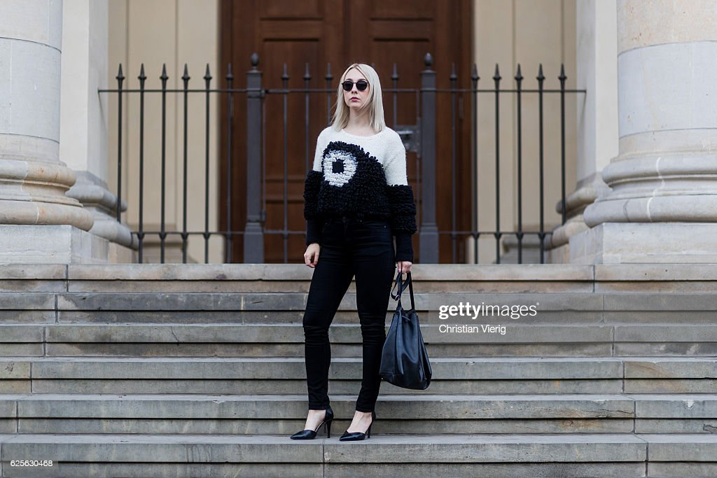 Leonie Markhorst (noanoir.com / @noanoir_) wearing a white black Lala Berlin sweater (Lina handknitted jumper), Long sleeves, crew neck with cuff, Long cuffs on the sleeves, black Weekday denim jeans, black Zign heels, black Ace & Tate sunglasses, black COS bucket bag on November 24, 2016 in Berlin, Germany.