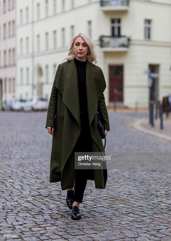 Leonie Markhorst (noanoir.com / @noanoir_) wears a khaki green coat from Ivy + Oak, black top from Uniqlo, black skinny denim jeans from Weekday, black shoes from Alexander Wang, black bag from Hi Eleven on October 31, 2016 in Berlin, Germany.