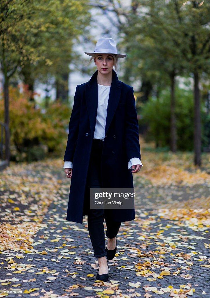 Leonie Markhorst (noanoir.com / @noanoir_) wears a navy vintage coat, white top Oak + Fort, black skinny jeans COS, black shoes from Oak + Fort, grey hat from Lack of Color on October 31, 2016 in Berlin, Germany.