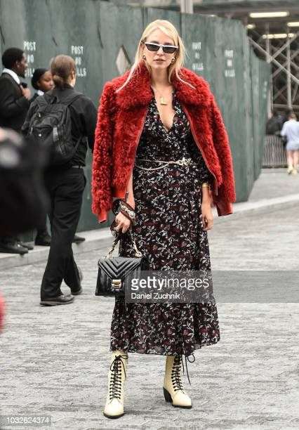 Leonie Sophie Hanne is seen wearing a red fur coat floral dress and beige boots outside the Michael Kors show during New York Fashion Week Women's...