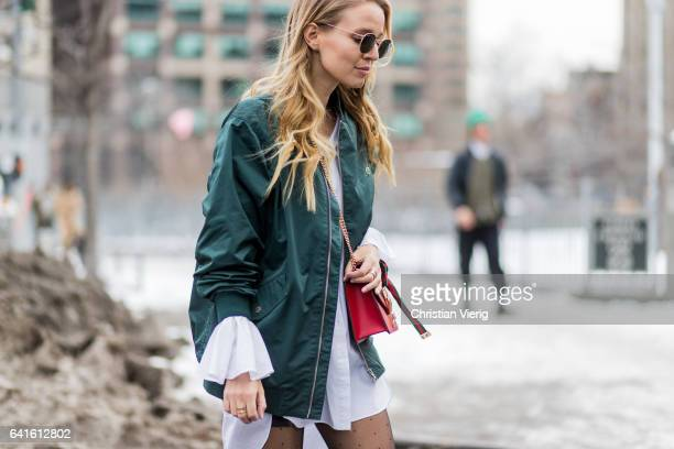 Leonie Sophie Hanne wearing a white blouse green bomber jacket Gucci bag black overknees tights outside Lacoste on February 11 2017 in New York City