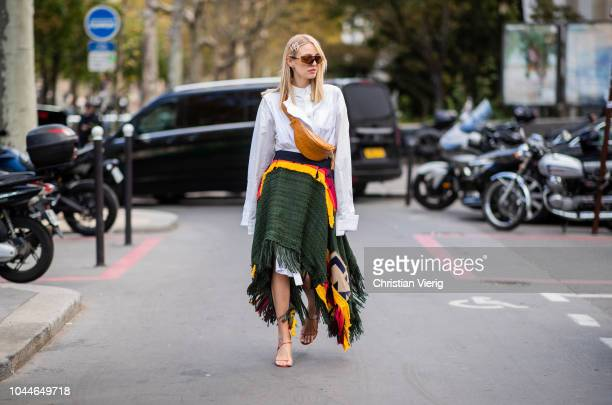 Leonie Sophie Hanne wearing asymmetric green skirt oversized button up dress with long sleeves brown fanny bag is seen outside Sacai during Paris...