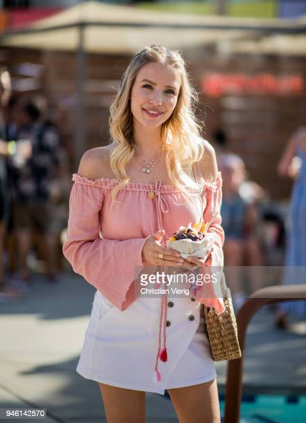 Leonie Sophie Hanne wearing cropped top white mini skirt is seen at Revolve Pool Party on April 13 2018 in Palm Springs California