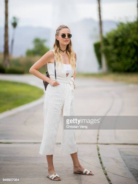 Leonie Sophie Hanne wearing white jumpsuit sandals backpack is seen at Revolve Festival on April 15 2018 in Indio California