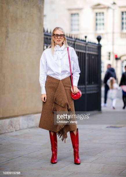 Leonie Sophie Hanne wearing white Valentino button shirt brown wrapped skirt red boots and bag seen outside Anya Hindmarch during London Fashion Week...