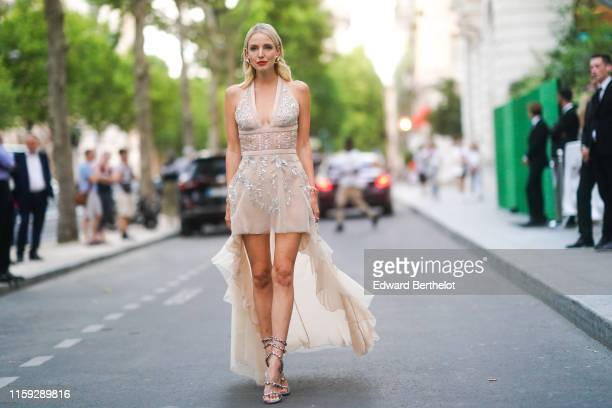 Leonnie Hanne wears earrings, a low neck lace dress with sequined inserts, heels shoes, outside AMFAR dinner, during Paris Fashion Week - Haute...