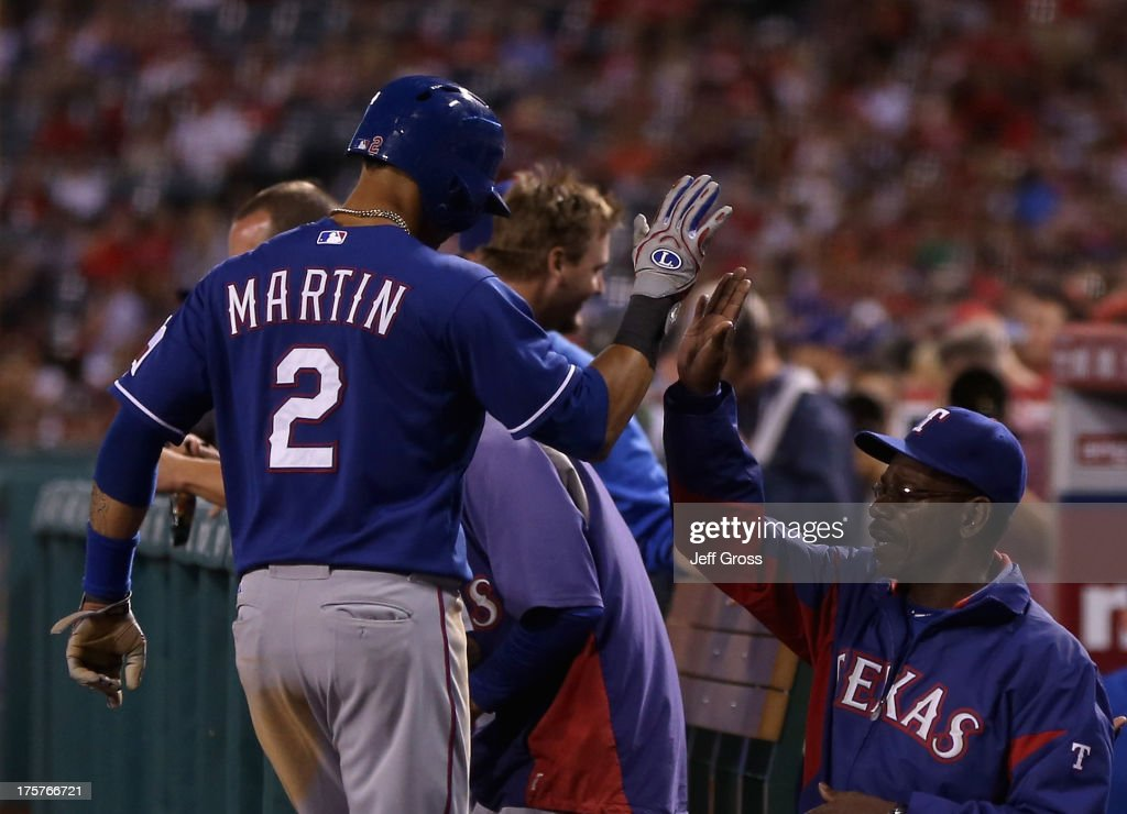Leonys Martin #2 of the Texas Rangers is congratulated by manager Ron Washington (R) after scoring a run in the third inning against the Los Angeles Angels of Anaheim at Angel Stadium of Anaheim on August 7, 2013 in Anaheim, California. The Rangers defeated the Angels 10-3.