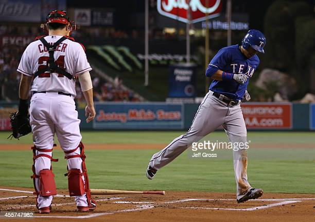 Leonys Martin of the Texas Rangers runs past catcher Hank Conger of the Los Angeles Angels of Anaheim and scores a run in the first inning at Angel...