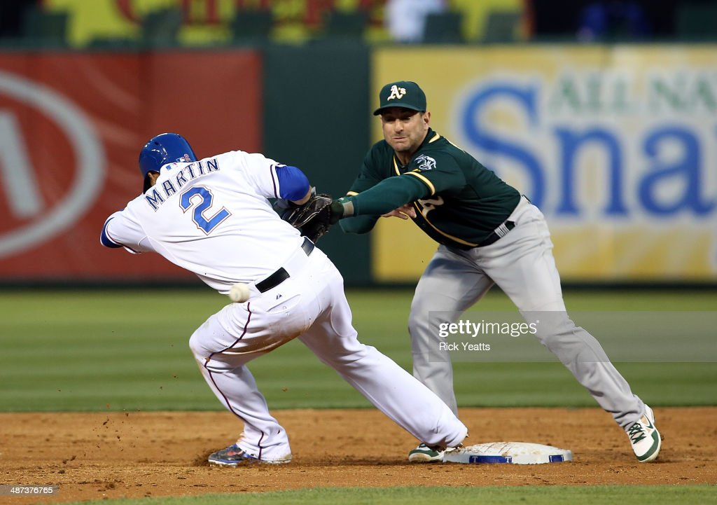 Leonys Martin #2 of the Texas Rangers steals third base on a wild throw to Nick Punto #1 of the Oakland Athletics at Globe Life Park in Arlington on April 29, 2014 in Arlington, Texas.
