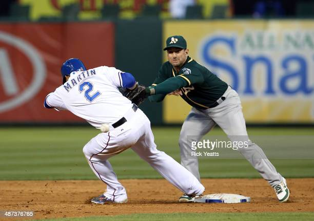 Leonys Martin of the Texas Rangers steals third base on a wild throw to Nick Punto of the Oakland Athletics at Globe Life Park in Arlington on April...