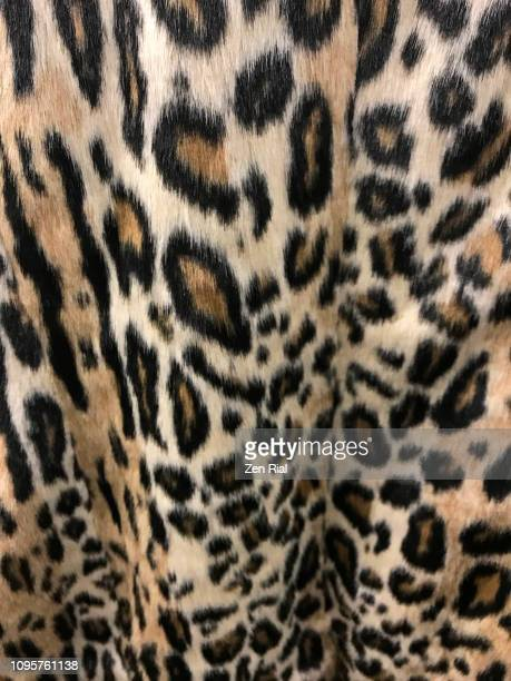 leopard print fake fur fabric- a winter coat - leopard print stock pictures, royalty-free photos & images