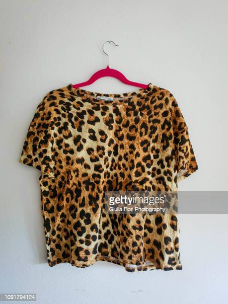 leopard t-shirt on a hanger - leopard print stock pictures, royalty-free photos & images
