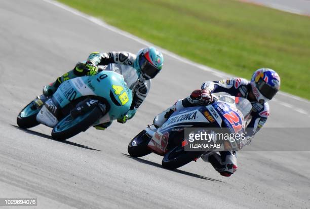 Leoperd Racing's rider Italian Lorenzo Dalla Porta rides to win next to Del Conca Gresini Moto3's Italian Fabio Di Giannantonio during the Moto3 race...