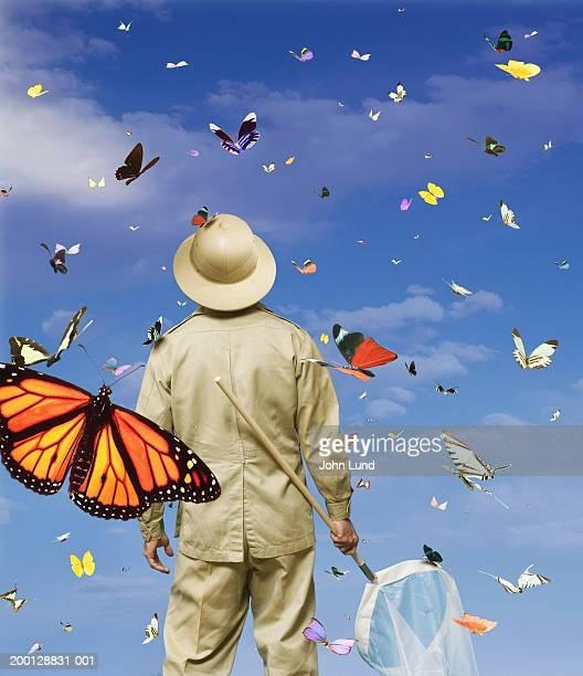 Lepidopterist holding net, standing amongst butterflies
