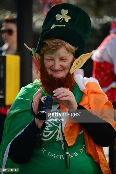 Leprechaun checking her video camcorder at the Saint Patrick's Day Parade in London