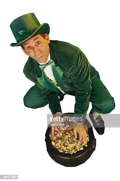 Leprechaun dipping hands into pot of gold