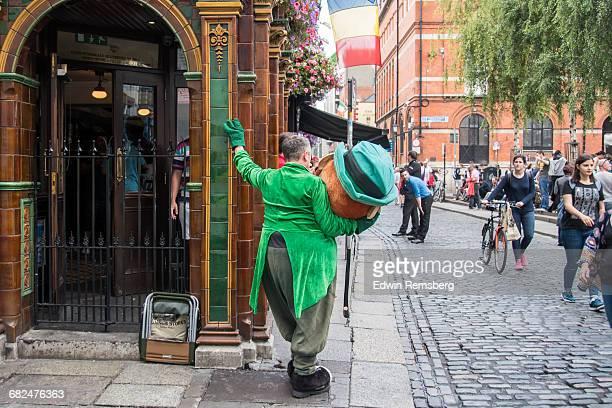 leprechaun mascot taking a break in dublin - leprechaun stock pictures, royalty-free photos & images