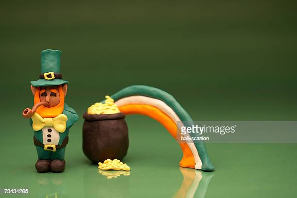Leprechaun smoking pipe by pot of gold at end of rainbow
