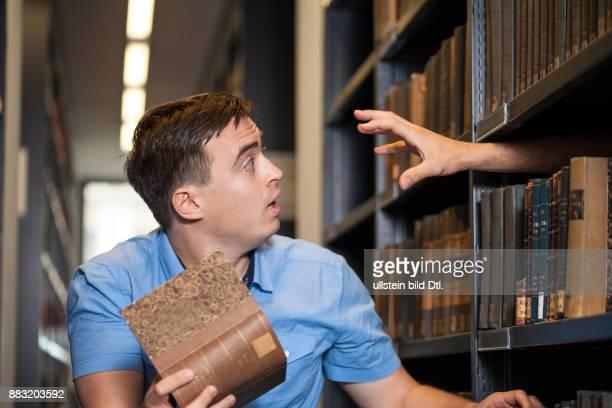 Lernender Student wird durch Hand erschrocken