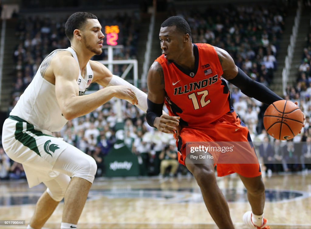 Leron Black #12 of the Illinois Fighting Illini handles the ball while defended by Gavin Schilling #34 of the Michigan State Spartans at Breslin Center on February 20, 2018 in East Lansing, Michigan.