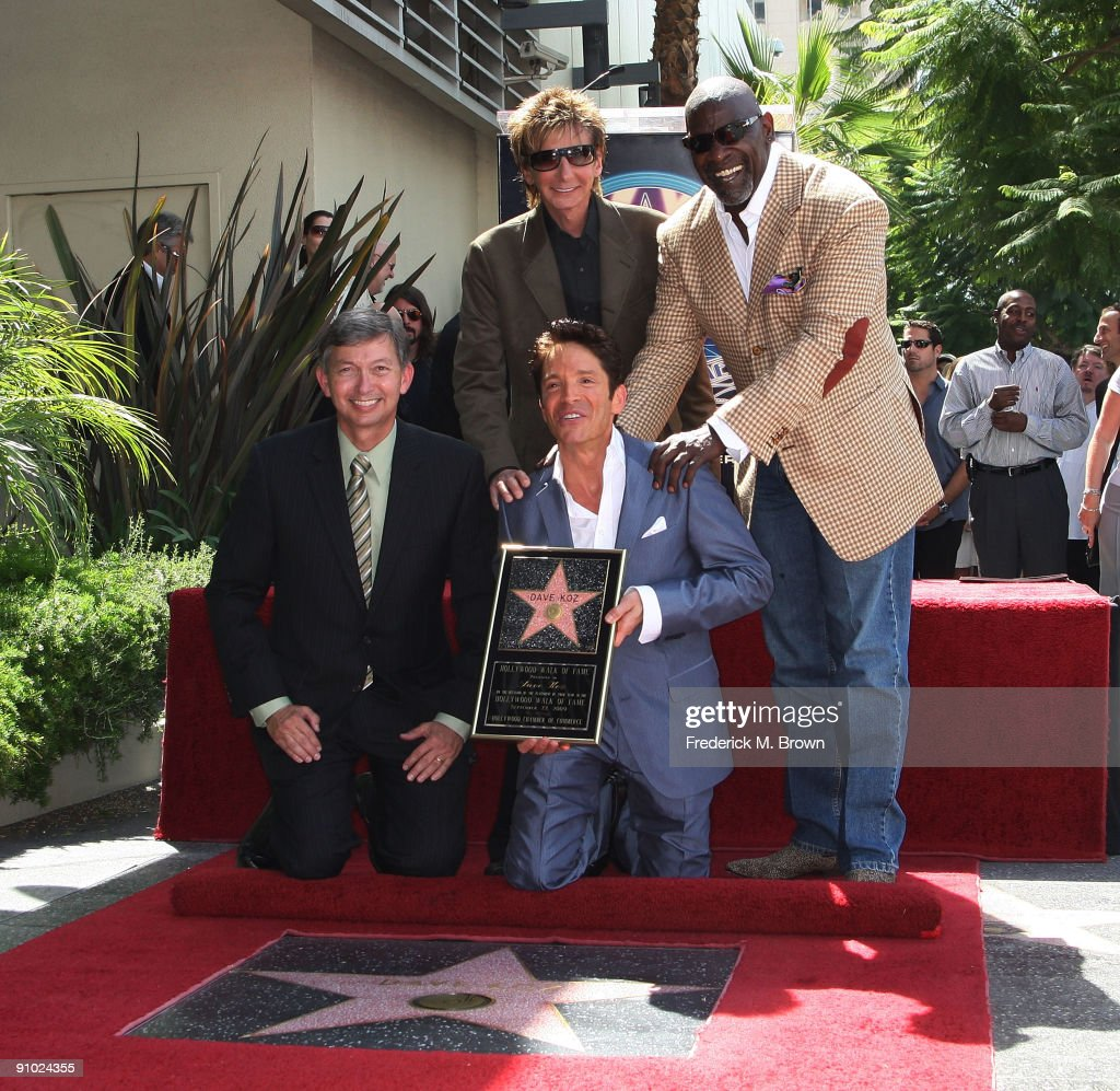 Leron Gubler, recording artist Dave Koz, Barry Manilow and Chris Gardner pose for photographers during ceremony honoring Koz with a star on the Hollywood Walk of Fame on September 22, 2009 in Los Angeles, California.