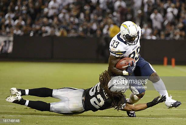 Le'Ron McClain of the San Diego Chargers gets tackled by Philip Wheeler of the Oakland Raiders in the fourth quarter of the season opener at...