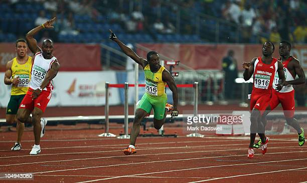Lerone Clarke of Jamaica celebrate winning gold in the men's 100 metres final next to Aaron RougeSerret of Australia silver medallist Mark...