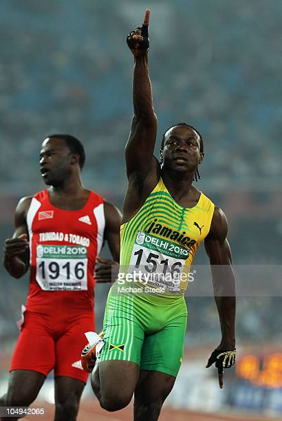 Lerone Clarke of Jamaica celebrates winning gold in the men's 100 metres final in front of Aaron Armstrong of Trinidad and Tobago at the Jawaharlal...