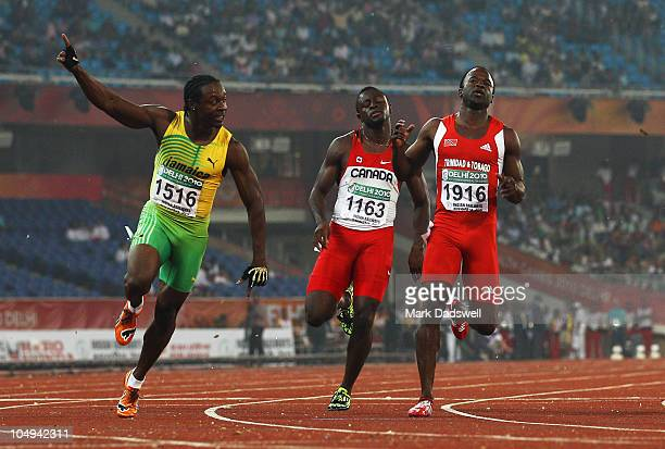 Lerone Clarke of Jamaica celebrates winning gold in the men's 100 metres final next to Sam Effah of Canada and Aaron Armstrong of Trinidad and Tobago...