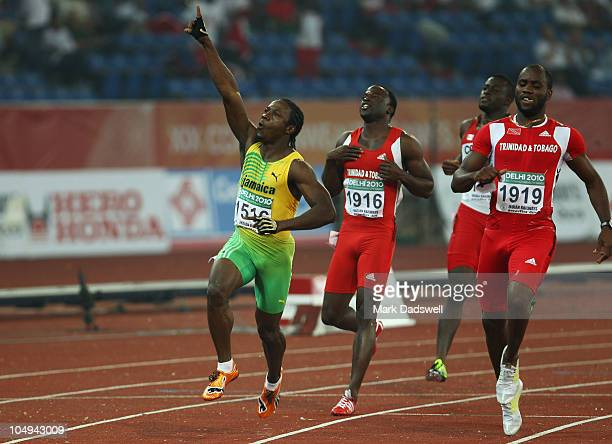 Lerone Clarke of Jamaica celebrates winning gold in the men's 100 metres final next to Aaron Armstrong of Trinidad and Tobago Sam Effah of Canada and...