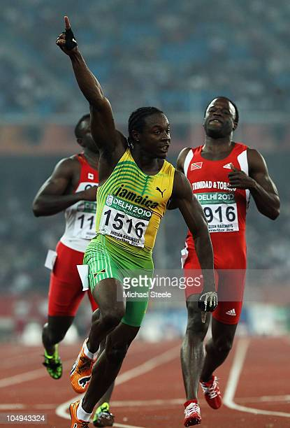 Lerone Clarke of Jamaica celebrates winning gold in the men's 100 metres final next to Sam Effah of Canada and bronze medallist Aaron Armstrong of...
